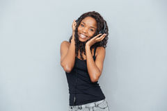 美国黑人的在耳机的妇女听的音乐 免版税库存图片