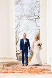 新娘和新郎走在专栏之间 免版税图库摄影