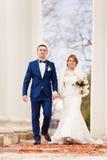 新娘和新郎走在专栏之间 免版税库存图片