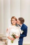 Жених целует невесту которая стоит между столбцами старого здания Стоковые Изображения