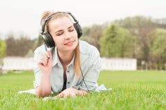 享受音乐的年轻美丽的妇女户外在耳机 免版税图库摄影