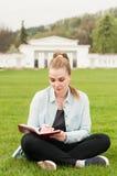 在她的坐在公园的日志的美好的妇女文字 图库摄影