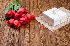 红色郁金香花束和一个礼物盒在一张木桌上 免版税库存图片