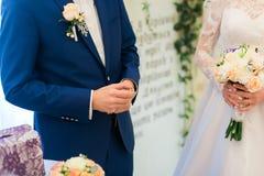 拿着婚戒的蓝色衣服的新郎在投入前它在新娘的手指 免版税库存图片