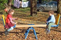 红色背心和她的兄弟的女孩跷跷板的 库存图片
