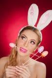 美丽的白肤金发的妇女当与室内天线的复活节兔子在红色背景,演播室射击 拿着三个色的鸡蛋的小姐 免版税图库摄影