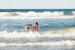 愉快的年轻夫妇有乐趣、男人和妇女在海滩的海 库存图片