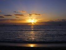 下降在海洋后的剧烈的日落发光在小船 库存图片