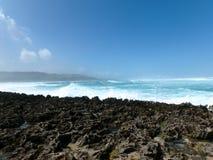 在珊瑚岩石岸的波浪断裂 免版税库存照片