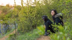 女孩与狗坐草甸 免版税库存图片