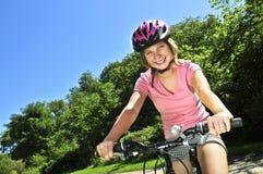 少年自行车的女孩 免版税图库摄影