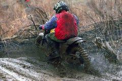 加速在泥铺跑道的摩托车越野赛竟赛者 免版税库存照片