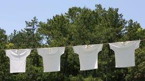 Άσπρες μπλούζες που κρεμούν για να ξεράνει απόθεμα βίντεο