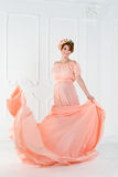 在桃红色晚礼服飞行的孕妇跳舞在风 挥动的织品,时尚射击 免版税图库摄影