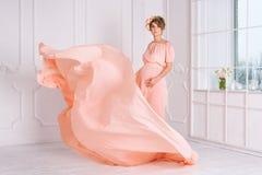 在桃红色晚礼服飞行的孕妇跳舞在风 挥动的织品,时尚射击 库存图片