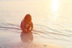 与沙子的小女孩戏剧在日落海滩 免版税库存图片