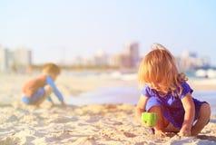 小女孩和男孩使用与在日落海滩的沙子 免版税库存图片