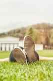 与横向说谎在草的妇女腿的无忧无虑的概念 免版税库存照片