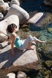 Συνεδρίαση γυναικών στο βράχο σχετικά με το νερό Στοκ φωτογραφίες με δικαίωμα ελεύθερης χρήσης