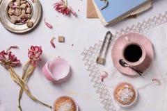 浪漫早餐、新鲜的咖啡、杯形蛋糕点心和桃红色花服务充满爱 顶视图 库存图片