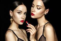 Δύο όμορφες νέες κυρίες με το κόκκινο κραγιόν Στοκ Φωτογραφίες