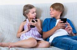 有户内智能手机的孩子 免版税库存图片