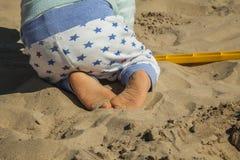 关闭使用与沙子玩具的男婴在海滩 查出的背面图白色 库存照片