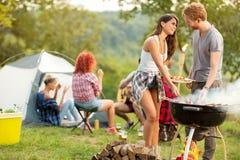 男性和女性爱恋互相看,当被烘烤的烤肉时 免版税库存照片