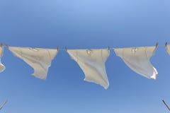 Άσπρες μπλούζες που κρεμούν στη σκοινί για άπλωμα Στοκ Εικόνες