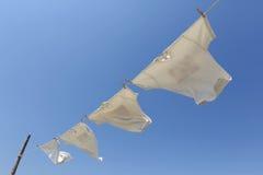 Άσπρες μπλούζες που κρεμούν στη σκοινί για άπλωμα Στοκ Εικόνα