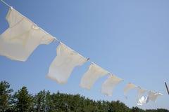 Άσπρες μπλούζες που κρεμούν για να ξεράνει Στοκ εικόνες με δικαίωμα ελεύθερης χρήσης
