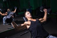 做卧推锻炼的英俊的运动员 免版税库存图片