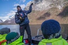 取笑解释关于挪威海湾的小船操作员 免版税库存图片