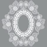 以大奖章的形式鞋带空的花框架 在灰色背景的白色有花边的布料 免版税库存照片