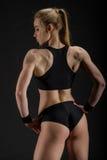 摆在黑色的年轻肌肉妇女 免版税库存照片