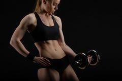 摆在有哑铃的演播室的年轻亭亭玉立的坚强的肌肉妇女 库存照片