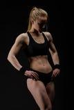 Молодая мышечная женщина представляя на черноте Стоковое Изображение
