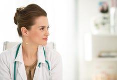 坐在一张书桌的女性医生画象在办公室 免版税库存照片