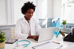 黑人女性医生佩带的白色外套在工作在办公室 库存照片