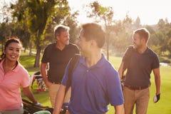 走沿航路运载的高尔夫球袋的小组高尔夫球运动员 免版税库存照片