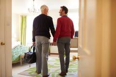 中部年迈的男性夫妇进来到旅馆客房,后面看法 库存图片