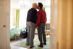 中部变老了男性夫妇亲吻在旅馆客房的,后面看法 免版税库存图片