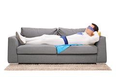 睡觉在长沙发的年轻超级英雄 库存图片