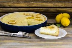 在一块白色板材的柠檬蛋糕在美好的木背景 库存图片