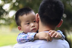 拥抱他的父亲的中国小男孩 男孩周道地看对一边 免版税库存照片