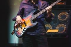 一个阶段的低音吉他球员在报告人附近 免版税库存图片
