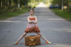 有玩具熊的逗人喜爱的小女孩在路的旅行家和手提箱 愉快 免版税库存照片