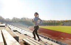 跑在楼上在体育场的愉快的少妇 免版税图库摄影