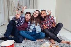 坐在屋子里和显示胜利标志的三个微笑的朋友 库存图片