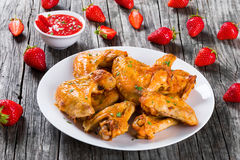 可口炸鸡飞过用草莓调味汁,特写镜头 免版税库存照片